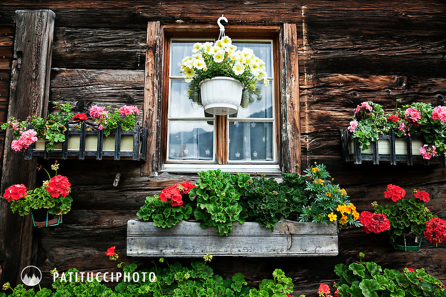 Typical Swiss chalet summer flowers hanging outside a house