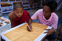 Young monk studying the work of a sandpainter in Bagan, Myanmar