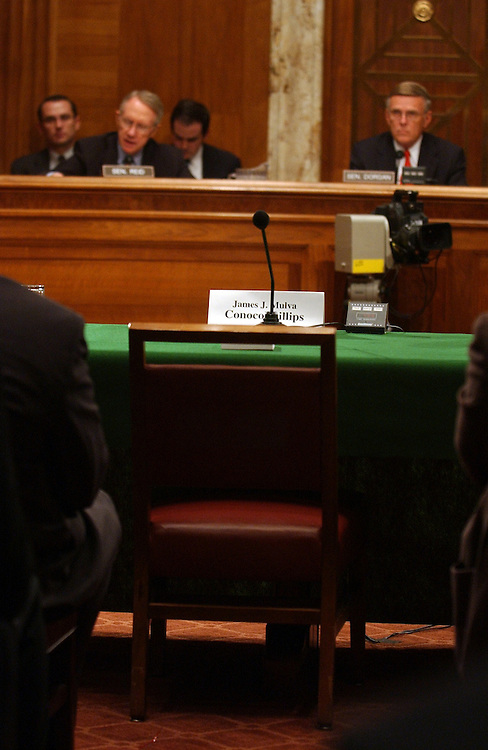 At a hearing of Democratic Policy Committee (DPC), the chair of James Mulva, CEO of Conoco Phillips sits empty during a hearing to examine the causes and impact of rising gas prices.  Senate Minority Leader Harry Reid, D-Nev., left, and chairman of the committee Byron Dorgan, D-N.D., look on.  John Hofmeister of Shell Oil Company and Lee Raymond of Exxon Mobil. also failed to show.