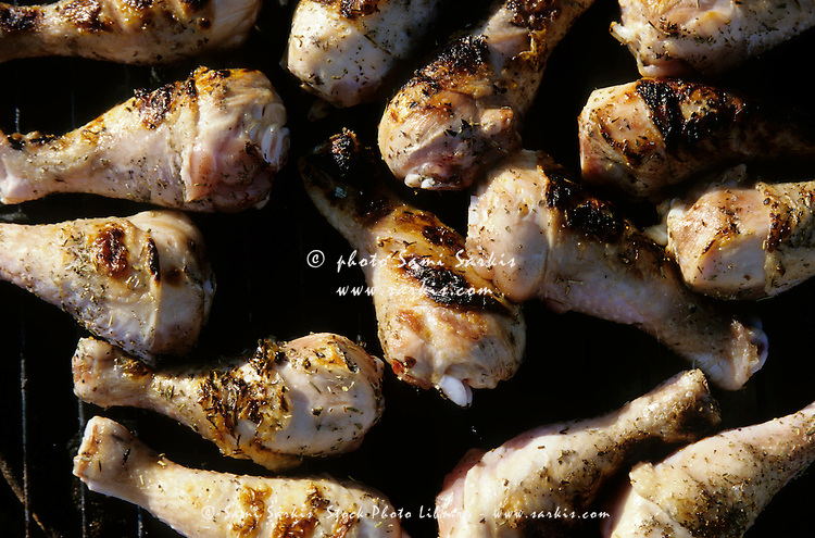 Chicken drumsticks being cooked on a barbecue for dinner.