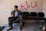 "Misrata revolutionary Yahya Mahmoud, 16, guards a deserted housing complex in Tawerga, Libya, Oct. 4, 2011. ""Every Misratan over the age of 15 is a fighter,"" said Yahya. Yahya and other members of the Al Watan Brigade sought to prevent the pro-Gaddafi Tawerga people back into the complex. In the wake of its success in repelling the long siege of Misrata by Qaddafi loyalists, the Misrata military council has not been afraid of asserting its authority in Misrata and further."