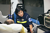 Switzerland. Canton Ticino. Morcote. A senior man lying down on an emergency medical stretcher is brought by ambulance to hospital for medical examination. The elderly man is suffering from deep vein thrombosis (DVT), which is a blood clot in the deep veins of the leg. The paramedic wears a blue uniforms and works for the Croce Verde Lugano. The woman is a volunteer specifically trained in emergency rescue. The volunteer looks at a monitor which controls a set of vital functions, such as  electrocardiogram, blood pressure's measurement, respiratory rate and pulse oximetry (oxygen saturation). The Croce Verde Lugano is a private organization which ensure health safety by addressing different emergencies services and rescue services. Volunteering is generally considered an altruistic activity where an individual provides services for no financial or social gain to benefit another person, group or organization. Volunteering is also renowned for skill development and is often intended to promote goodness or to improve human quality of life. 27.01.2018 © 2018 Didier Ruef