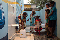 Local residents fill up their water cans at the iJal water station in Ambedkar Nagar in Medak, Telangana, India.