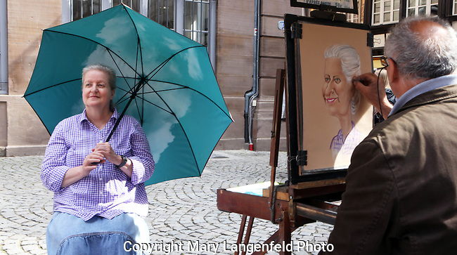 A woman has her portrait done in the courtyard of the Strasbourg, France Cathedral.