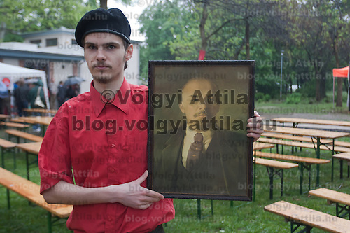 A supporter of the Hungarian Communist Party holds a picture of former soviet leader Vladimir Lenin after their march together celebrating Labour Day in Budapest, Hungary on May 01, 2011. ATTILA VOLGYI