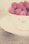 a pretty vintage teacup filled with ripe fresh pink raspberries