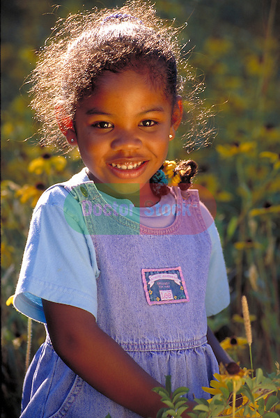 portrait of smiling young girl in field of flowers