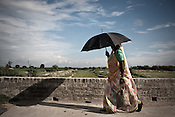 A woman walks past the dried up Mourawa Rajwaha Canal in Unnao, Rae Bareli in Uttar Pradesh, India. The 4 month annual rainfall is crucial to summer sown crops as 60% of the farmlands are rainfed. North India experienced scanty rainfall in late june to july. Till August, rain in India has been 26% below 5 year average. Late rains moist the fields but it is not enough for rice, sugarcane, oilseeds and pulses. Late rains also damage the alternate crops that need less water.