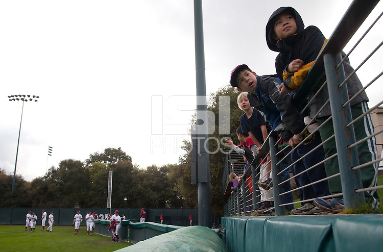 STANFORD, CA - March 25, 2011: Kids watch Stanford baseball players run to the dugout prior to Stanford's game against Long Beach State at Sunken Diamond. Stanford lost 6-3.