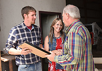 NWA Democrat-Gazette/FLIP PUTTHOFF <br />Garrett and Amanda Gittlein receive the 2017 Benton County Farm Family of the Year from State Rep. Dan Douglas (R-Bentonville) (right). The Gittleins raise cattle and hay at their farm near Maysville and do custom hay baling.