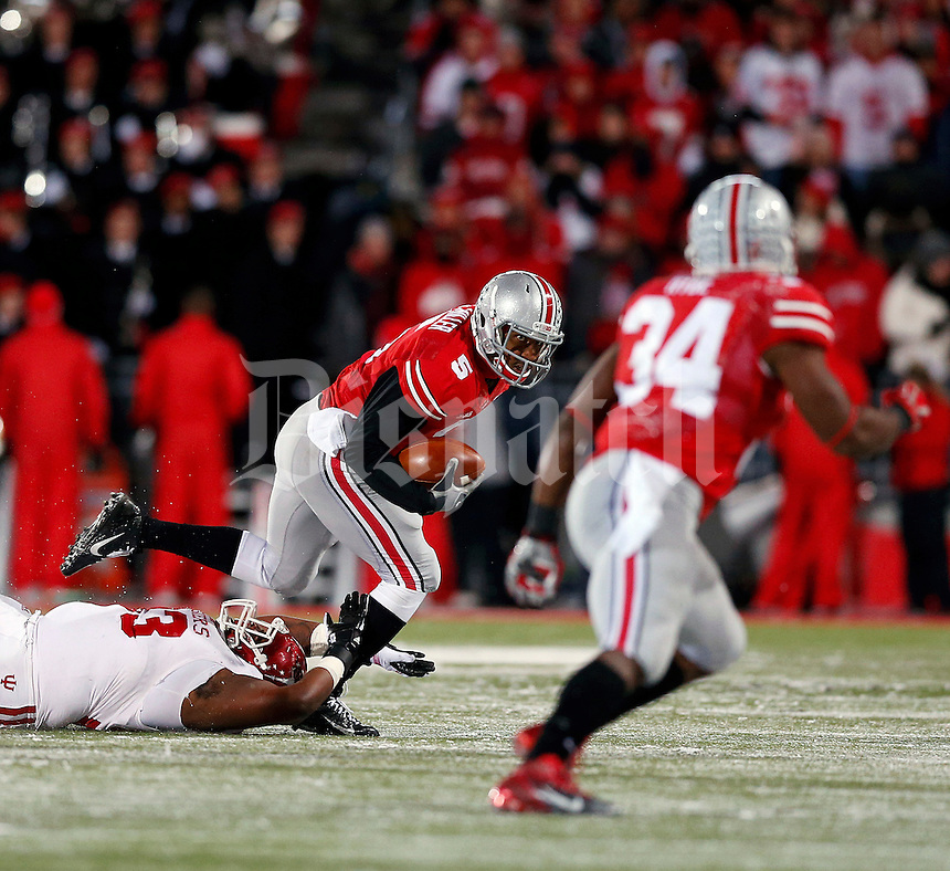 Ohio State Buckeyes quarterback Braxton Miller (5) slips out of the tackle from Indiana Hoosiers defensive tackle Ralphael Green (93) during the third quarter of their college football game at Ohio Stadium in Columbus, Ohio on November 23, 2013.  (Dispatch photo by Kyle Robertson)