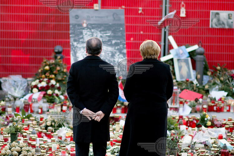 Francois Hollande, President of France, and German Chancellor Angela Merkel (right), in front of candles and flowers left in memory of the terror attack at the Breitscheidtplatz Christmas market on 19 December 2016.