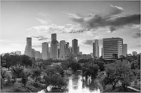 On a warm September morning, this black and white image of downtown Houston, Texas, shows the skyline view from a pedestrian bridge over Buffalo Bayou. The sun would soon peek over the trees in the east and flood the area with light. (It got pretty hot real fast, as well!) But it was a peacful time in the largest city in Texas.