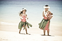 Children practicing hula at the beach with leis on