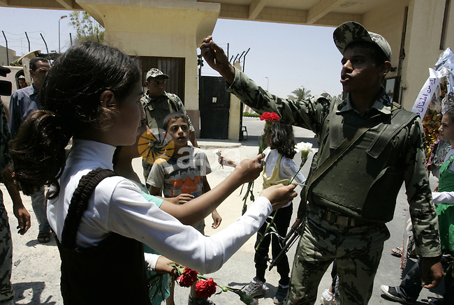 Palestinian children hand out flowers to Egyptian soldiers during a rally in front of the Rafah border crossing with Egypt in the southern Gaza Strip on June 21, 2011, demanding it to be open permanently and without restrictions or conditions on the passengers. Photo by Abed Rahim Khatib