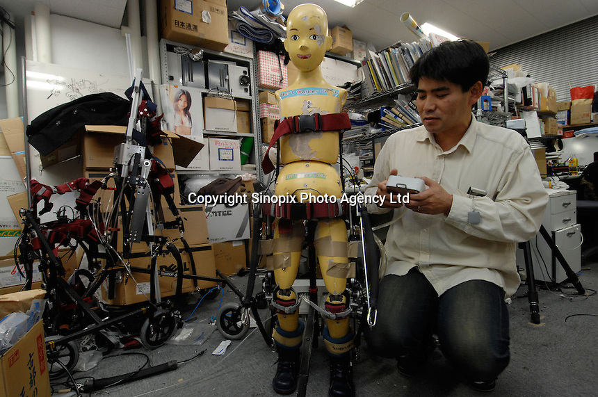 "Dr Hiroshi Kobayashi poses next to the ""Active Walker""   at the Department of Mechanical Engineering, Tokyo University of Science. The Active Walker is a suit that will enable children who are disabled and unable to use leg muscles to walk."