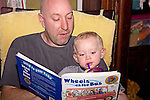 "Bald headed Dad reads to blonde two year old boy book ""Wheels on the Bus"" sitting in rocking chair at home."