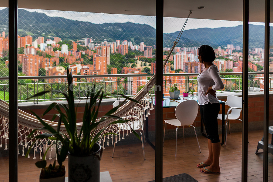 A Colombian cam model, known as Flora Bella, overlooks El Poblado neighborhood from a balcony of her apartment in Medellín, Colombia, 21 November 2016. With the traditional adoration of female beauty in Colombia, together with rapidly developing telecommunications technologies, the millennial generations of Colombian girls have turned the city of Medellín during the past few years into a one of the world centers of webcam modelling, a booming interractive sex industry. Thousands of young women stream everyday via websites that allow the global viewers to personally interract with a model and to pay them for sexually related acts. Although the core of the show is always based on stripping, the crucial part of a cam girl's success is communication. Cam models who have the ability of light conversation, flirting and entertaining the viewer earn thousands of dollars a month and have moved far beyond the borders of sexuality. Sharing their whole lives in a constant interaction with their online clients, they have built regular relationships in the cyberspace.