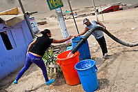 A Peruvian girl pays a water distribution worker to fill plastic barrels with drinking water on the dusty hillside of Pachacútec, a desert suburb of Lima, Peru, 21 January 2015. Although Latin America (as a whole) is blessed with an abundance of fresh water, having 20% of global water resources in the the Amazon Basin and the highest annual rainfall of any region in the world, an estimated 50-70 million Latin Americans (one-tenth of the continent's population) lack access to safe water and 100 million people have no access to any safe sanitation. Complicated geographical conditions (mainly on the Pacific coast), unregulated industrialization (causing environmental pollution) and massive urban poverty, combined with deep social inequality, have caused a severe water supply shortage in many Latin American regions.