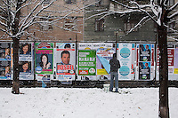 Milano: un uomo attacca cartelloni per la campagna elettorale
