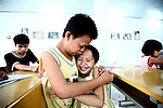 A boy hugs a girl at a center for children who have been affected by dioxin exposure in the village of Hoa Nhon, near Da Nang, Vietnam.  The Da Nang Association of Victims of Agent Orange/Dioxin says that more than 1,400 children around the city suffer from mental and physical disabilities because of dioxin exposure, a legacy of the U.S. military's use of Agent Orange and other herbicides during the Vietnam War more than 40 years ago. About 60 children attend the Hoa Nhon center each day. Many have mental disabilities, while others cannot hear and speak. It usually takes a year before a new child will make friends and start interacting with others, says Phan Thanh Tien, the association's president. The Vietnam Red Cross estimates that 3 million Vietnamese suffer from illnesses related to dioxin exposure, including at least 150,000 people born with severe birth defects since the end of the war. The U.S. government is paying to clean up dioxin-contaminated soil at the Da Nang airport, which served as a major U.S. base during the conflict. But the U.S. government still denies that dioxin is to blame for widespread health problems in Vietnam and has never provided any money specifically to help the country's Agent Orange victims. May 29, 2012.