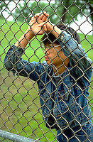 Cambodian/Am age 15 looking through chain link fence at school.  St Paul Minnesota USA