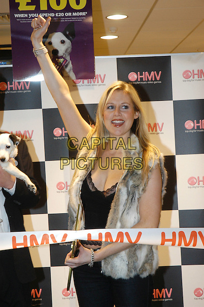 ABI TITMUSS.Opening HMV in Chelmsford.December 2nd, 2004.half length, fur vest, scissors, ribbons, arm in air, gesture.www.capitalpictures.com.sales@capitalpictures.com.©Capital Pictures