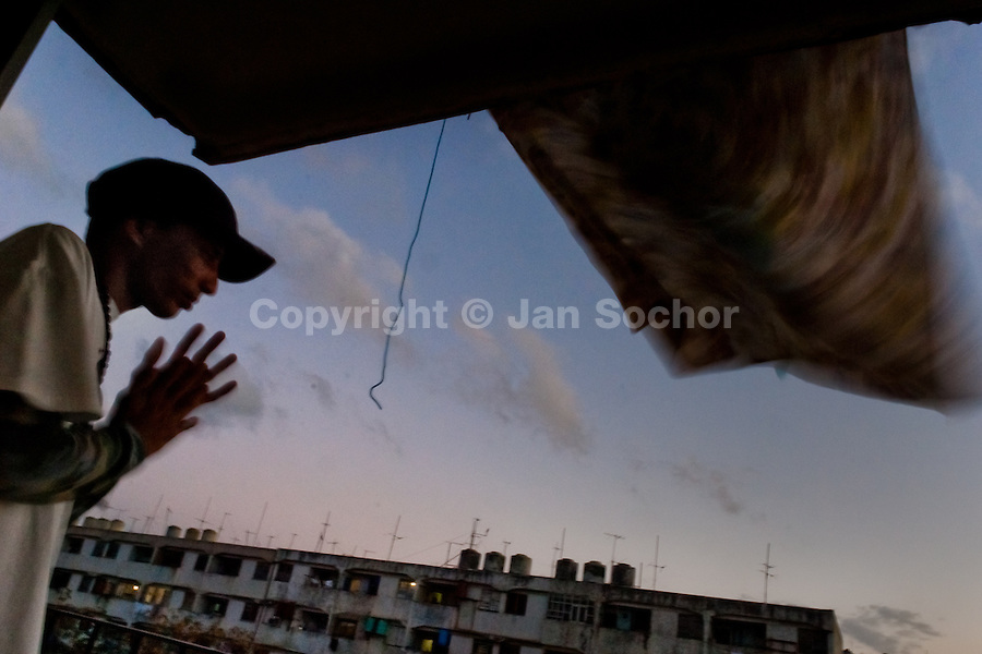 """A young Cuban man stands on the balcony of his apartment in Alamar, a public housing complex in the Eastern Havana, Cuba, 9 February 2009. The Cuban economic transformation (after the revolution in 1959) has changed the housing status in Cuba from a consumer commodity into a social right. In 1970s, to overcome the serious housing shortage, the Cuban state took over the Soviet Union concept of social housing. Using prefabricated panel factories, donated to Cuba by Soviets, huge public housing complexes have risen in the outskirts of Cuban towns. Although these mass housing settlements provided habitation to many families, they often lack infrastructure, culture, shops, services and well-maintained public spaces. Many local residents have no feeling of belonging and inspite of living on a tropical island, they claim to be """"living in Siberia""""."""