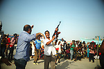 "ZANZUR, Libya 4th September 2011:..A Libyan Arab fires his Kalashnikov to control the crowd during a Libyan Red Crescent food drop. .."" You have to use force,"" he told me afterwards. ..""They are savages.""..Ayman Oghanna"