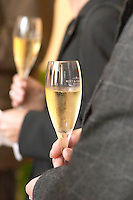 Champagne cocktail at Moet & Chandon (Epernay, France). A man holding a champagne flute glass engraved with Moet & Chandon, another glass unsharp in the background