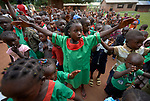 A girl spreads her arms as she and other students sing while they gather in the morning at the Catholic Church-sponsored Abangite Nursery School in Yambio, South Sudan.