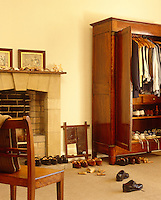 In this bedroom framed antique prints, a stone fireplace and large mahogany antique wardrobe create an unashamedly masculine feel