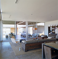 The open-plan living area leads out through glass doors to a large covered terrace