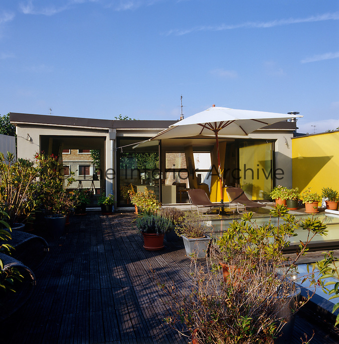 At the top of the house sliding glass doors lead from a garden room to the roof garden where an umbrella and sun-loungers have been arranged on wooden decking