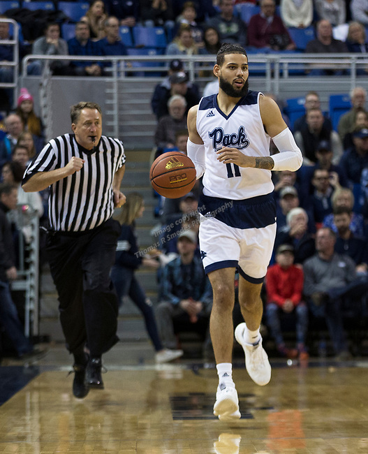 Nevada forward Cody Martin (11) brings the ball up the court                          against Utah State in the first half of an NCAA college basketball game in Reno, Nev., Wednesday, Jan. 2, 2019. (AP Photo/Tom R. Smedes)