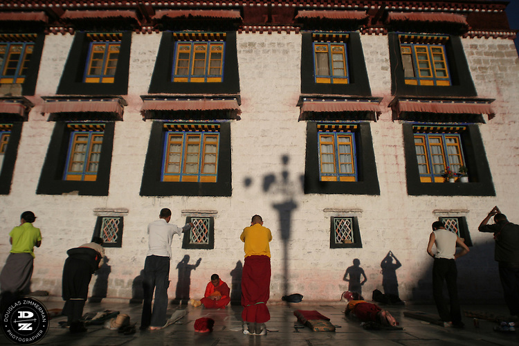 Buddhist pilgrims prostrate in front of the Jokhang (also known in Tibetan as Tsuglhakhang) at sunset in Barkhor Square in Lhasa, Tibet. The Jokhang is considered the most revered religious structure in Tibet.  Photograph by Douglas ZImmerman