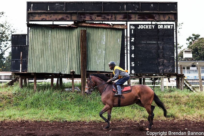 Jockey Daniel Tanui rode past the jockey board at the Ngong Racecourse during  morning exercise.  The racecourse opened in 1954, is the last bastion of horseracing in Kenya. Nairobi, Kenya. March 15, 2013. Photo: Brendan Bannon