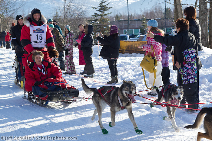Charley Bejna and team run past spectators on the bike/ski trail during the Anchorage ceremonial start during the 2013 Iditarod race.    Photo by Britt Coon/IditarodPhotos.com
