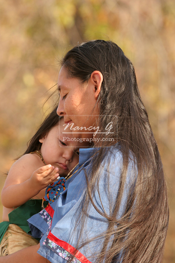 A Native American Indian mother holding and comforting her todler who was upset