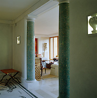 View into the drawing room past the elegant turquoise scagliola columns of the entrance hall which has a black and white mosaic floor
