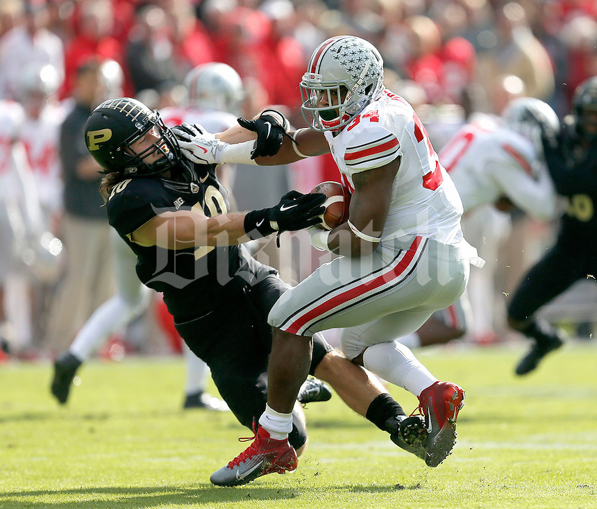 Ohio State Buckeyes running back Carlos Hyde (34) gets past Purdue Boilermakers linebacker Sean Robinson (10) during the first half of the NCAA football game at Ross-Ade Stadium in West Lafayette, IN on Saturday, November 2, 2013. (Columbus Dispatch photo by Jonathan Quilter)