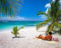 Dominikanische Republik, Isla Saona, Laguna Canto de la Playa, junge Frau liegt allein an einem einsamen Strand, liest Illustrierte   Dominican Republic, Saona Island, Laguna Canto de la Playa, young woman lying at deserted beach, reading
