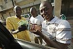 Africa, Afrika, Senegal, 17-09-2011, Dakar, Dakkar, Straatbeeld, markten langs de kant van de weg, sloppenwijk, bus vervoer, drukte, kleurrijk, Zwarthandelaars van geld wisselen Euro's door het raam van de auto.. foto: michael Kooren/HH