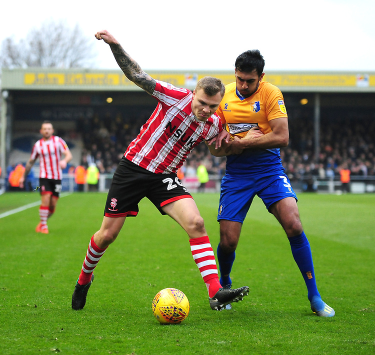 Lincoln City's Harry Anderson vies for possession with Mansfield Town's Malvind Benning<br /> <br /> Photographer Andrew Vaughan/CameraSport<br /> <br /> The EFL Sky Bet League Two - Lincoln City v Mansfield Town - Saturday 24th November 2018 - Sincil Bank - Lincoln<br /> <br /> World Copyright © 2018 CameraSport. All rights reserved. 43 Linden Ave. Countesthorpe. Leicester. England. LE8 5PG - Tel: +44 (0) 116 277 4147 - admin@camerasport.com - www.camerasport.com