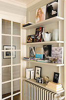 In the dining room an open shelf containing books, magazines and an eclectic collection of objects takes up minimal space above a radiator