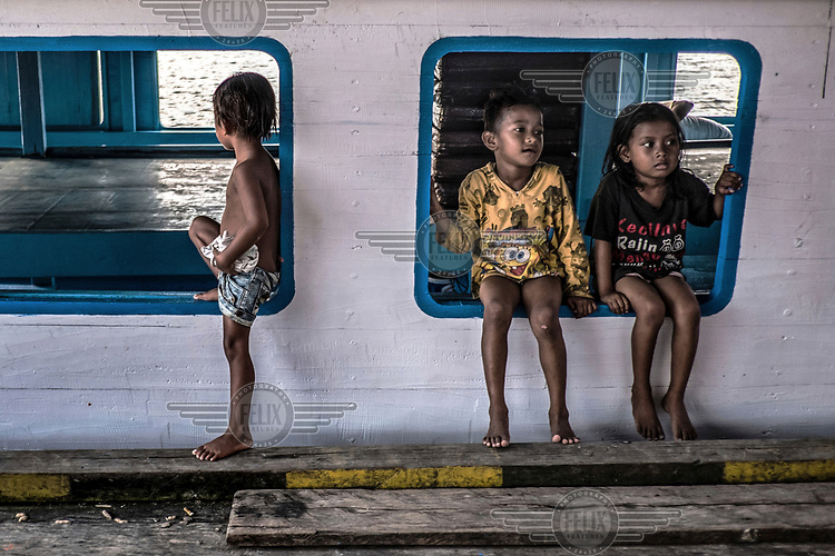 Bajau children sit in the windows of a ferry that connects the Togean Islands with mainland Sulawesi.