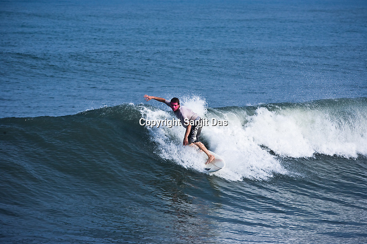 "Jeeru Krishna Dasa, one of the Krishna devotees from the Kaliya Mardana Krishna Ashram is seen surfing on the Arabian Sea on the beach front of Mangalore, Karnataka, India.  ..Krishna devotees in the Gaudiya Vaishnava tradition of Hinduism, they are known collectively as the ""surfing swamis."" The ""surfing ashram"" is growing in popularity and surfing here is a form of meditation, a spiritual practice leading to heightened states of awareness."