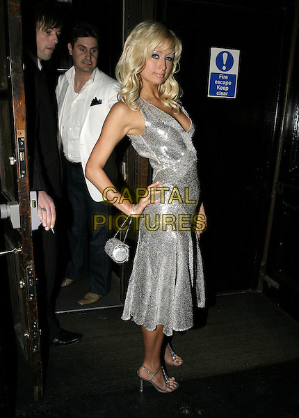 PARIS HILTON.Arrives at Kaberet Club, London, SW1,.May 16th 2005..full length silver sequined dress shimmering glittery sparkling sequins bag beaded round hand on hip.Ref: AH.www.capitalpictures.com.sales@capitalpictures.com.©Adam Houghton/Capital Pictures.