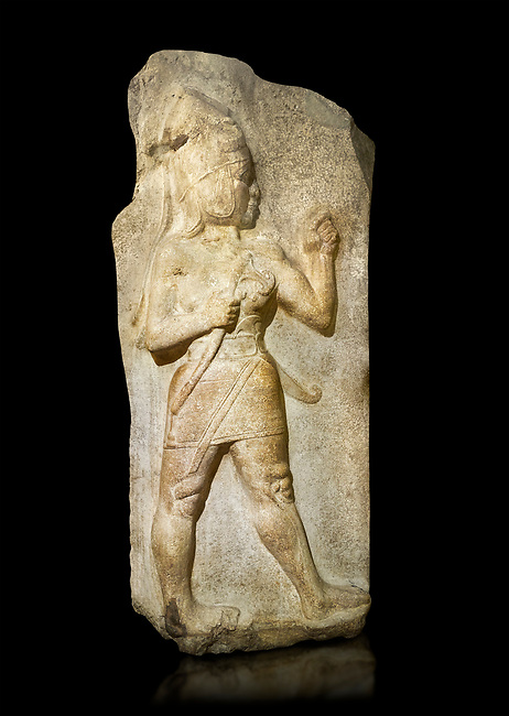 Relief of God of War. Limestone, Kings Gate, Hattusa ( Bogazkoy ). 14th - 13th Century BC. Anatolian Civilisations Museum, Ankara, Turkey.<br /> <br /> The warrior depicted in high relief is dressed in a decorated skirt. The relief takes place on the interior part of the King's gate facing city, to the east of the city walls. He carries a crescent-handled short sword in his belt. The relief is identified as god depiction since the horns on the headdress are the indication of a god.  <br /> <br /> Against a black background.