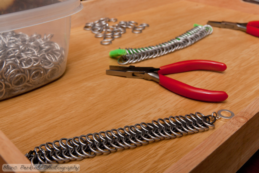 My friend has started making chain mail, and this is his work area.  The bracelet in front is finished; the two rows of rings in back will be a chest piece.